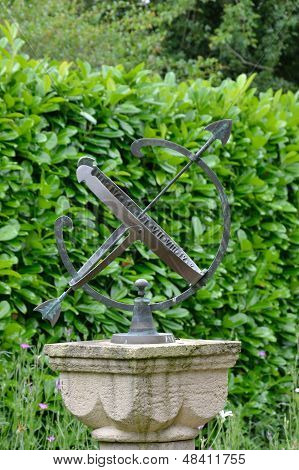 sun dial with hedge in bacground
