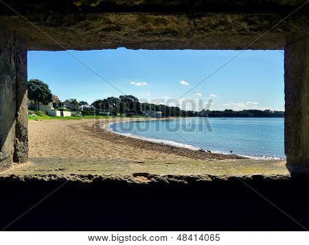 View through a bunker window onto a beach