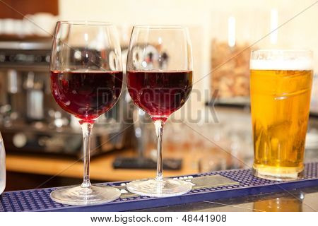 two glasses of wine and glass of beer