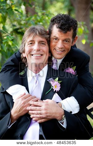 Handsome gay couple in love, posing for an outdoor wedding portrait.