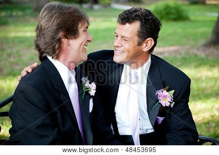 Gay couple celebrating their marriage together outdoors.