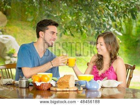 couple having breakfast at home with garden in the background
