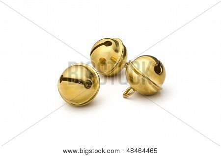 three golden sleigh bells on a white background