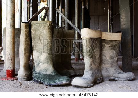 Dirty Galoshes At A Construction Site