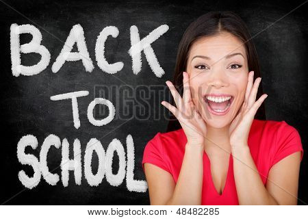 Back to School. Student screaming yelling BACK TO SCHOOL with text on blackboard. Female university college student standing in front of chalkboard. Ethnic Asian Caucasian woman student.