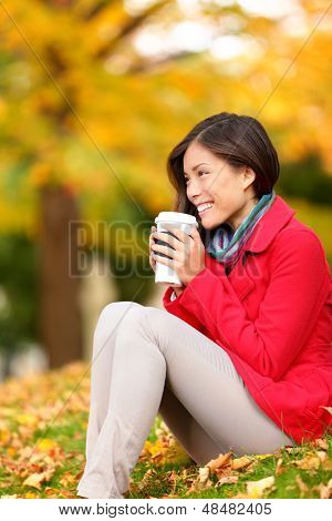 Autumn woman drinking coffee in fall forest. Girl sitting relaxing enjoying hot drink, coffee or tea, from disposable cup. Beautiful female outdoor in autumn colors. Multiracial Asian Caucasian, 20s.