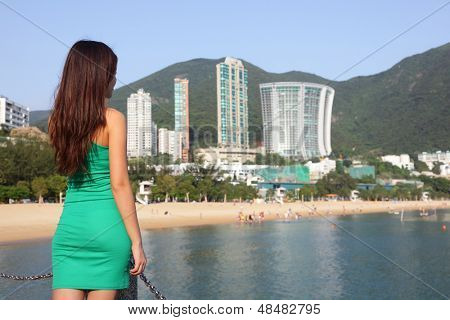 Hong Kong tourist woman at Repulse Bay beach. Beautiful Asian woman in summer dress enjoying view. Hong Kong travel and tourism concept.