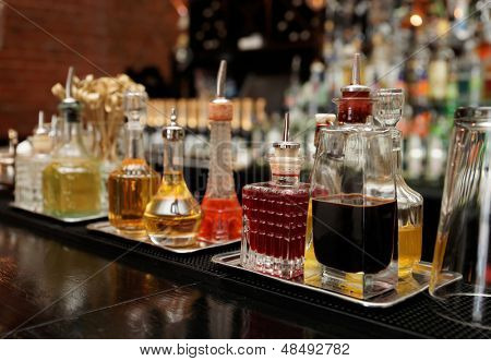 Bitters and infusions on bar counter, bar bottles in blurred background