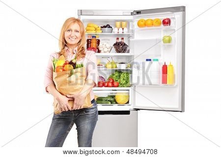 Smiling mature woman holding a paper bag full of groceries in front of refrigerator, isolated on white background