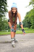 foto of inline skating  - Happy young girl enjoying roller skating rollerblading on inline skates sport in park - JPG
