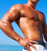 stock photo of pectorals  - A man with a beautiful muscular body relaxing on the beach - JPG