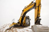 foto of hoe  - closeup of earthmover excavator stand on quarry pile sand pit soil earth covered with snow in winter - JPG