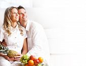 foto of healthy eating girl  - Young love couple with fruits in the comfortable apartment - JPG