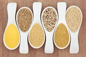 Healthy grain food selection in white porcelain spoons over papyrus background. Polenta, buckwheat,