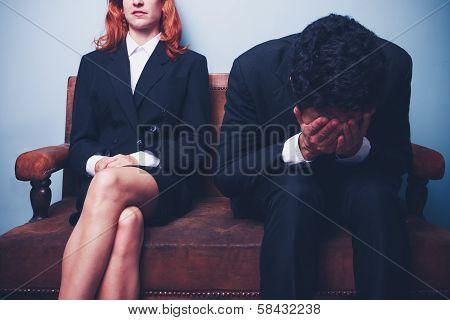Nervous Businessman Sitting Next To Confident Businesswoman