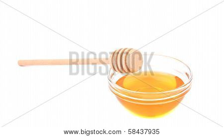 Wooden spoon on bowl with honey.