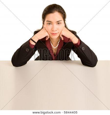 Frau stützte sich auf Schreibtisch beim Blick in die Kamera