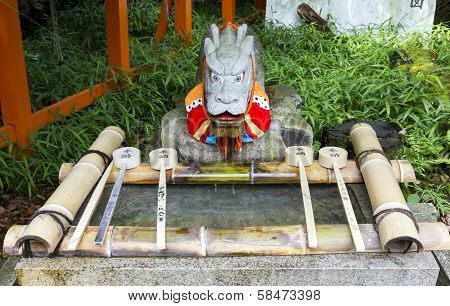 Purification Ladles And A Dragon Statue In A Shinto Shrine In Japan