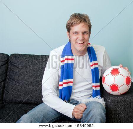 Sonriente a joven viendo fútbol en casa