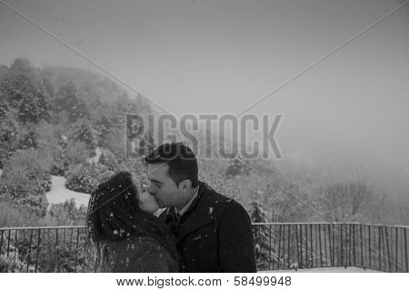 Couple Kissing Under The Snowflakes
