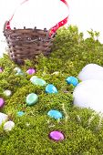image of chocolate hills  - Colored Foil Wrapped Chocolate Easter Eggs On Green Moss Hill with Wicker Basket