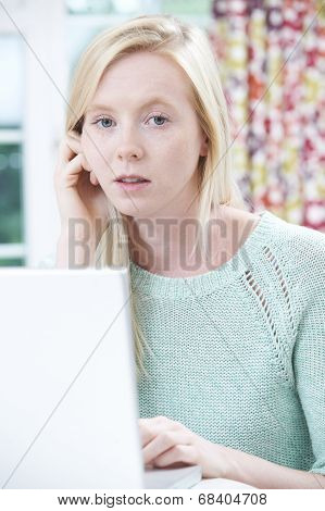 Worried Teenage Girl Using Laptop At Home
