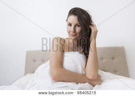 Portrait of sensuous woman covered with bedsheet in bed