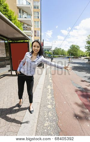 Full length portrait of smiling businesswoman hailing taxi on street