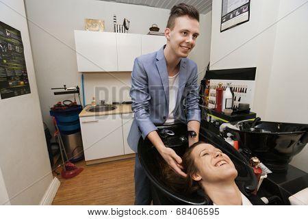 Smiling male hairstylist washing female customer's hair in salon