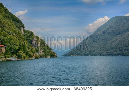 Lake Lugano seen for the deck of a boat. To the left is Mt. Bre and Gandria and to the right is Landessa and Alpe Trevino, with Dolomites in the distance straight ahead.