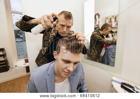 Professional barber using hairspray on male customer in shop