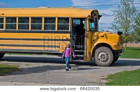 young girl with school bus