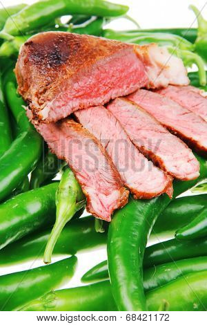 meaty food : grilled meat steak sliced over green hot chili peppers on a white back