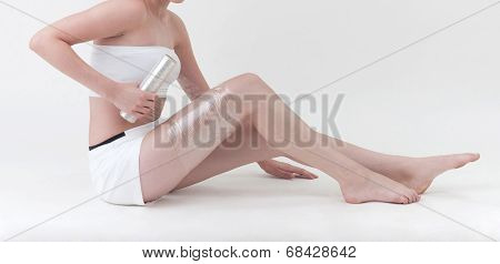 woman wrapping her leg with plastic wrapper