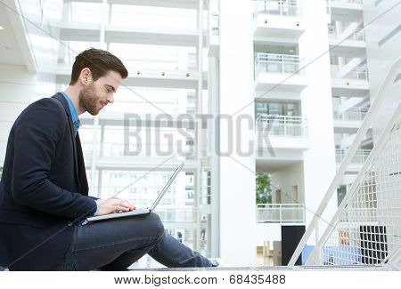 Young Man Working On Laptop Indoors