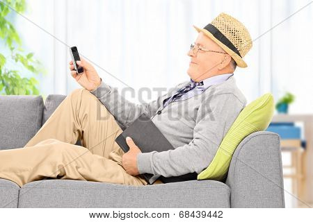 Senior gentleman sending an sms via cell phone at home