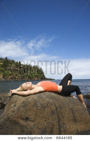 Attractive Young Woman Lying On Rock At Beach