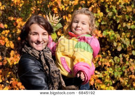 Mother hold daughter on hands on walk in autumnal park