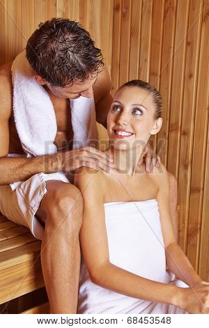 Man giving smiling woman a massage in hotel sauna