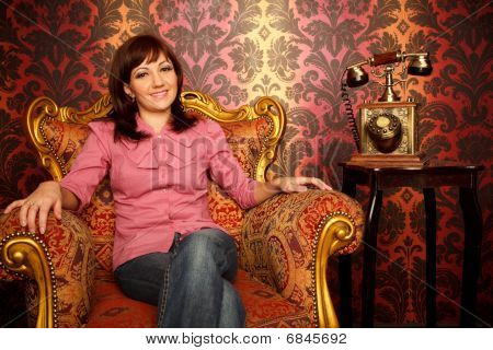 Portrait Of Girl Sitting In Armchair With An Retro Phone. Interior In Retro Style.