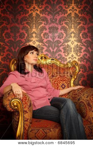 Portrait of girl sitting in armchair. Interior in retro style. Looking aside. Vertical format.