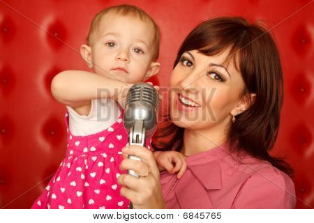 Portrait of mother and doughter with microphone on rack against red wall