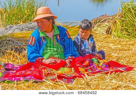 PUNO, PERU, MAY 5, 2014 - Local woman in traditional attire sits by ground with her son and offers some embroidery craft on floating Uros islands on Lake Titicaca