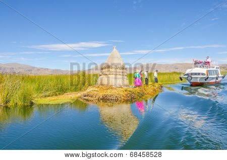PUNO, PERU, MAY 5, 2014 - Local people in traditional attires welcome tourists coming by boats from Puno town to visit floating Uros islands on Lake Titicaca