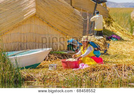 PUNO, PERU, MAY 5, 2014 - Women in traditional attire does her laundry by hand on floating Uros islands on Lake Titicaca