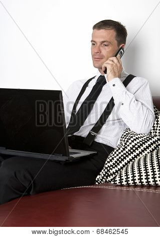 Businessman Sitting On Couch With Phone And Labtop