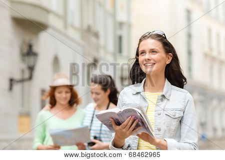 tourism, travel, leisure, holidays and friendship concept - smiling teenage girls with city guide, map and camera outdoors