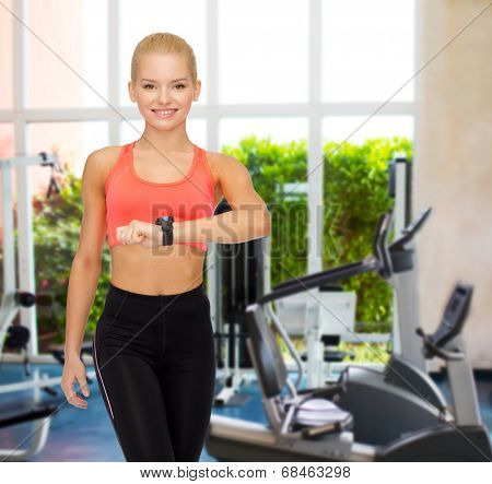 fitness, technology and exercising concept - smiling woman with heart rate monitor on hand