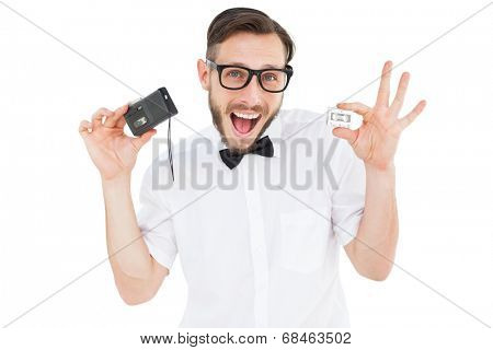 Geeky hipster holding a retro tape cassette player on white background