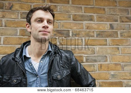Mid-adult man in a leather jacket looking away